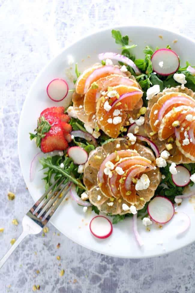This summer citrus salad has layers of flavor from the spicy arugula, earthy radishes, sweet oranges and grapefruit to tangy goat cheese and pistachios. Paleo, Gluten-Free and Refined Sugar-Free. | realsimplegood.com