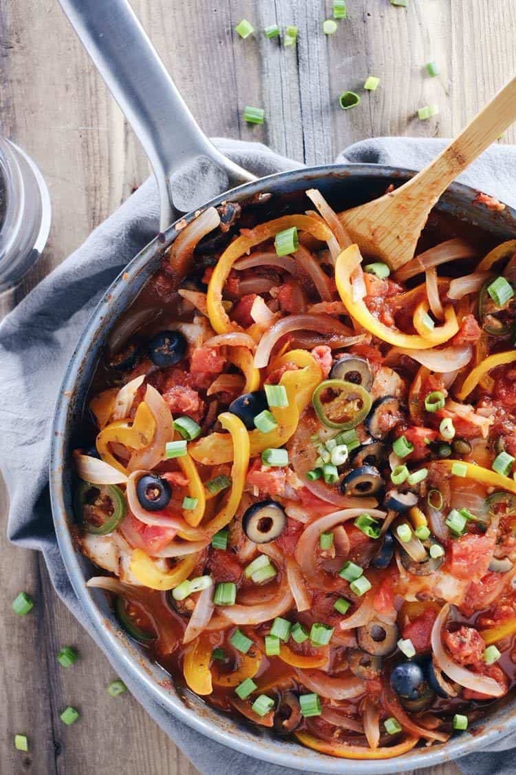 We love this veracruz style fish skillet because it is a refreshing way to enjoy fish! It's bursting with flavors of fresh peppers, onions, jalapeños, olives and a spicy sauce. Paleo, Gluten-Free + Dairy-Free. | realsimplegood.com