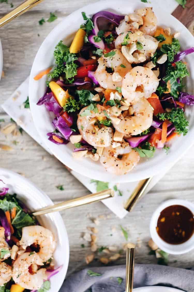 This chopped Thai shrimp salad is like eating the rainbow! It's packed with fruit, veggies and fresh herbs! Make this nutritious salad filled with kale, cabbage, bell pepper, carrots, mango and cilantro. It's super easy and quick to make! Paleo, Whole30 + Gluten-Free, Dairy-Free. | realsimplegood.com
