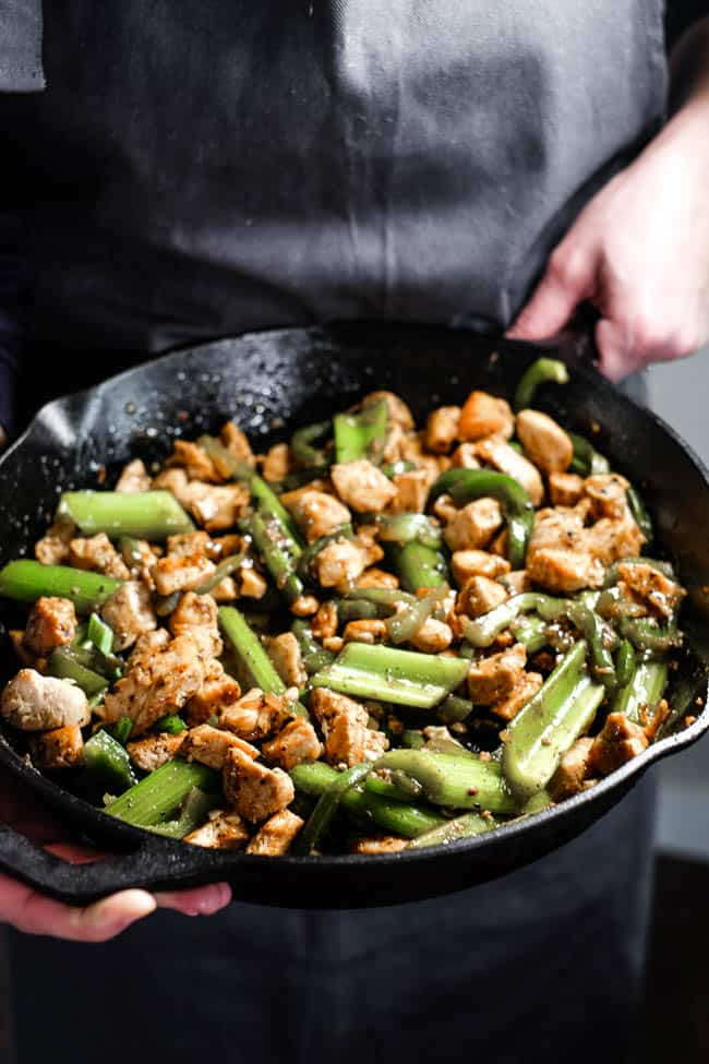 Hands holding skillet full of chicken, celery and bell pepper