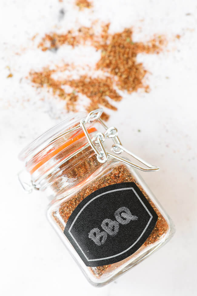 BBQ seasoning in a jar with label laying on counter with seasonings around it