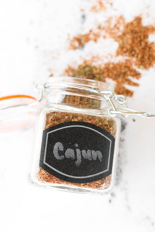 Cajun seasoning in a jar with label laying on counter with some spilling out of the top