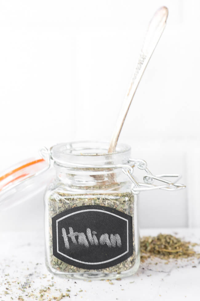 Italian seasoning in a jar with label with spoon coming out of the top