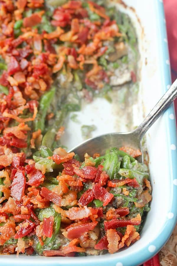 Green bean casserole with bacon on top in a casserole dish