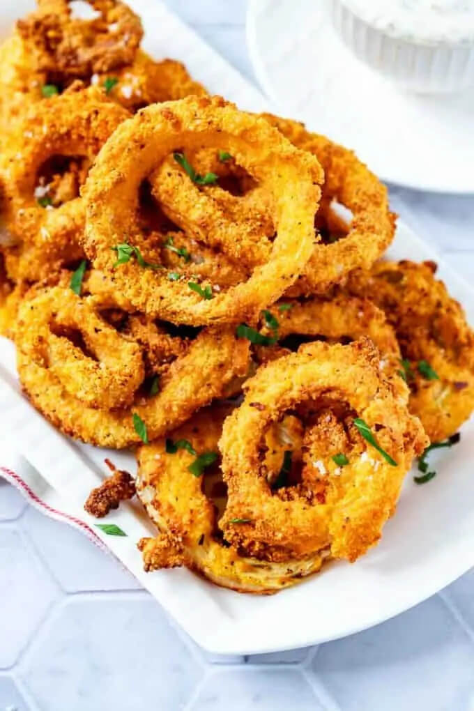 Onion rings on a plate with chopped parsley