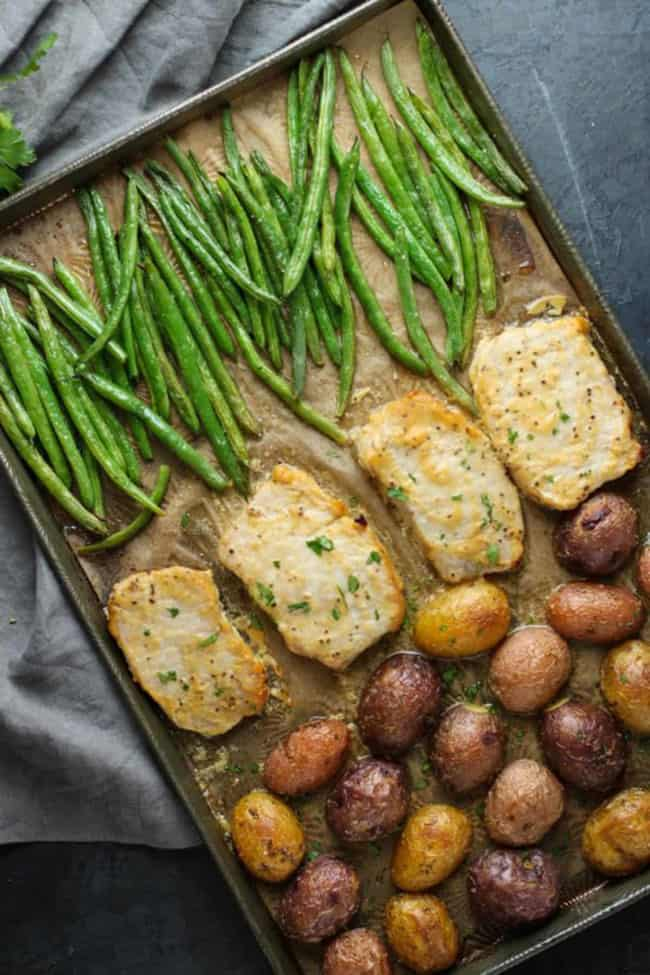 Green beans, pork chops and potatoes arranged separately on a pan.