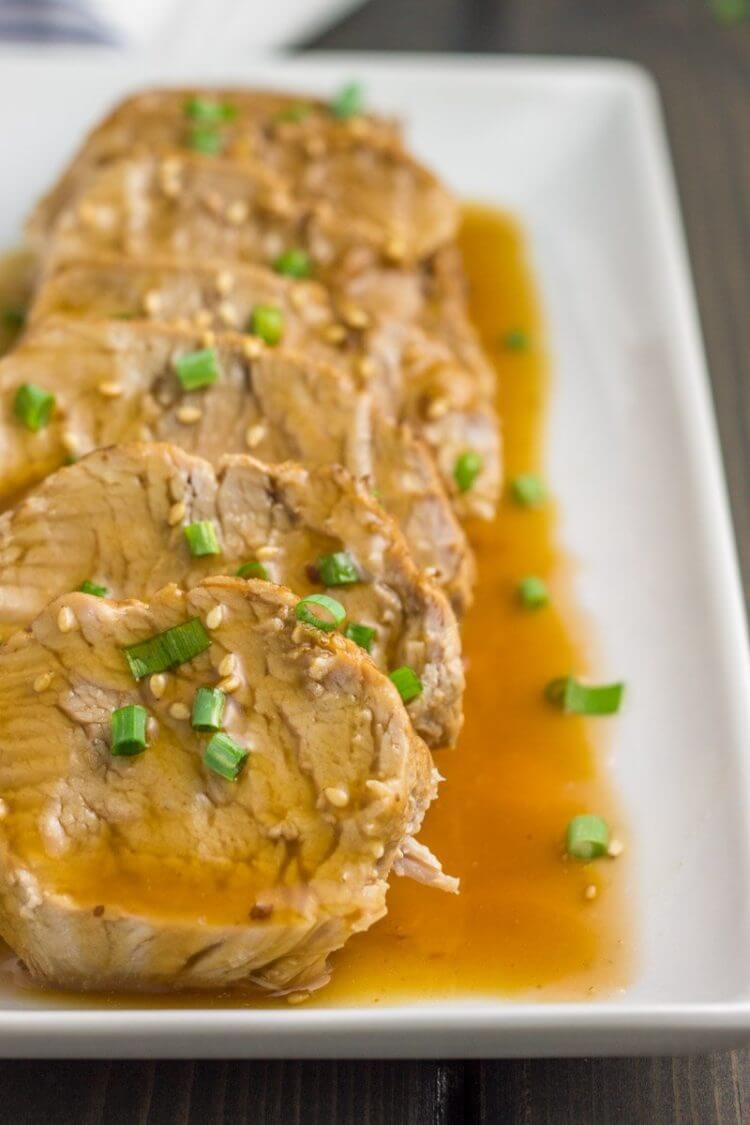 Instant pot teriyaki pork tenderloin on a plate stacked in a row with sauce angle shot