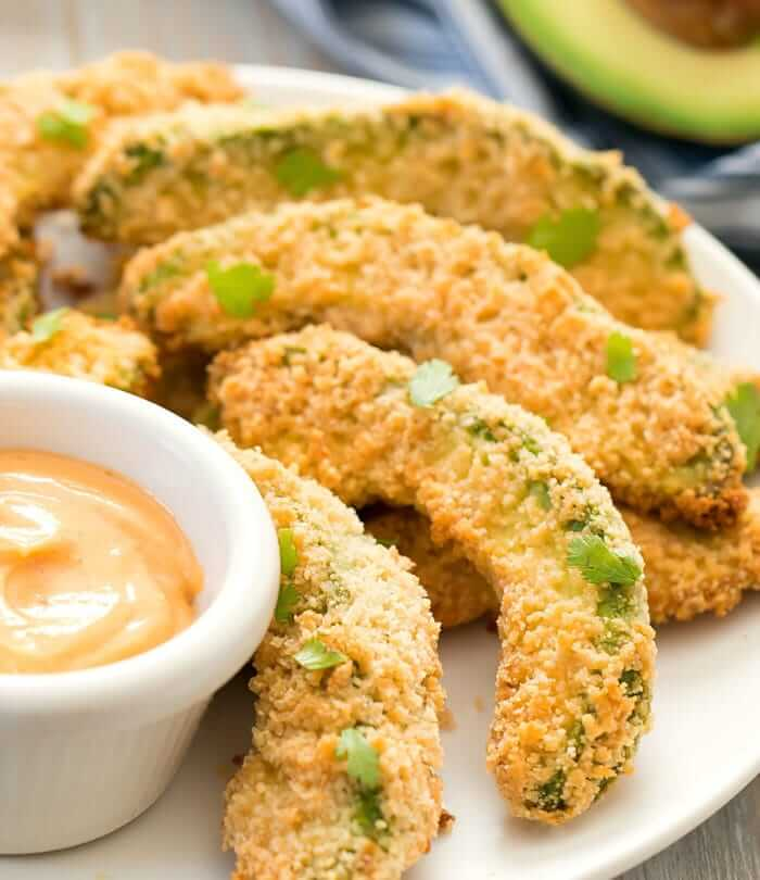 Breaded avocado wedges on a plate with dipping sauce