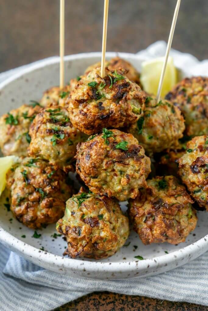 Pile of meatballs on a plate with lemon wedges and skewers in a few meatballs