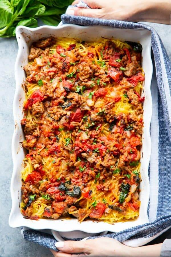 Creamy sausage basil tomato spaghetti squash overhead shot with hands holding dish - healthy casseroles