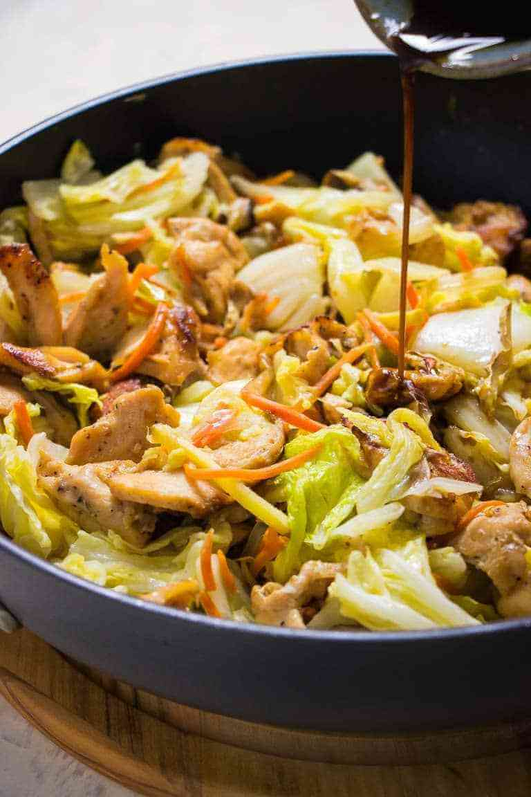 Cabbage stir fry in skillet with sauce being poured in