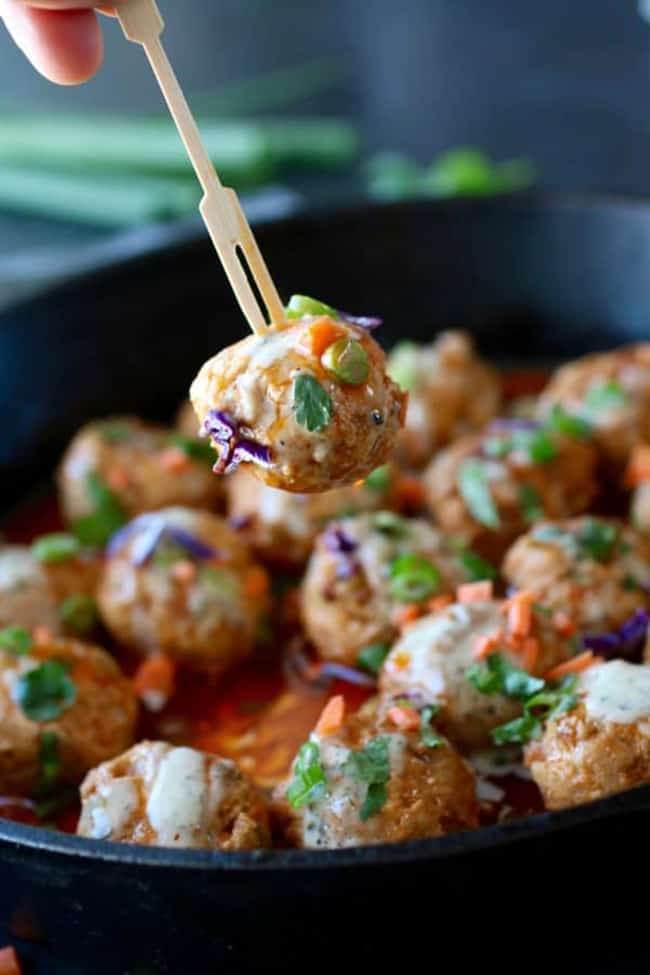 Buffalo chicken meatballs with one meatball held up close
