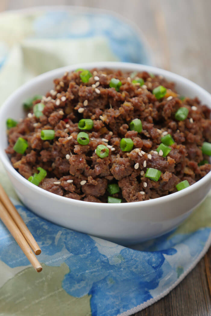 Bowl of korean beef bulgogi with sliced green onion and sesame seeds