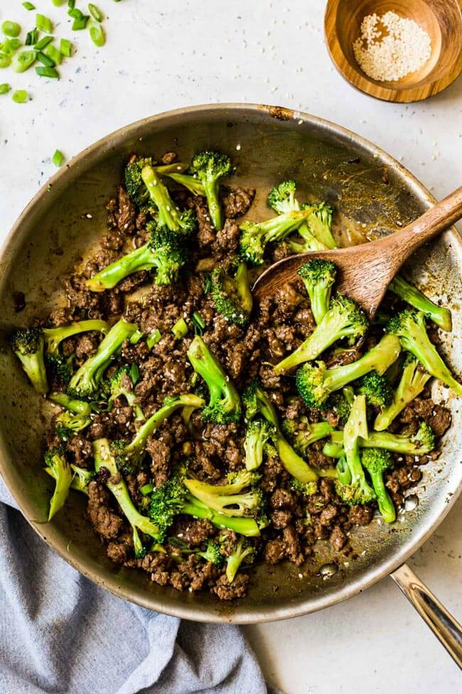 Ground beef and broccoli stir-fry in a skillet with wooden spoon
