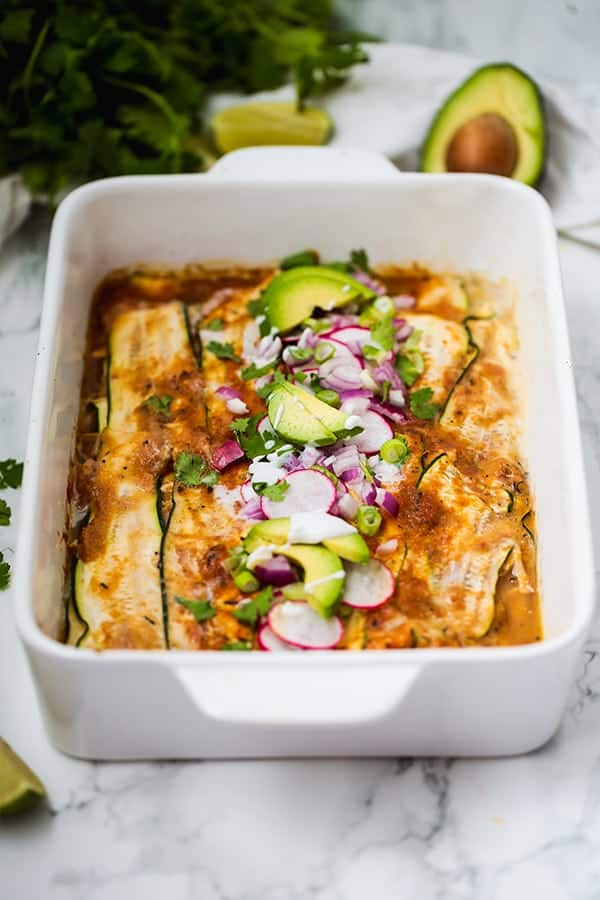 Zucchini chicken enchilada casserole in dish with avocado and radish toppings - healthy casseroles