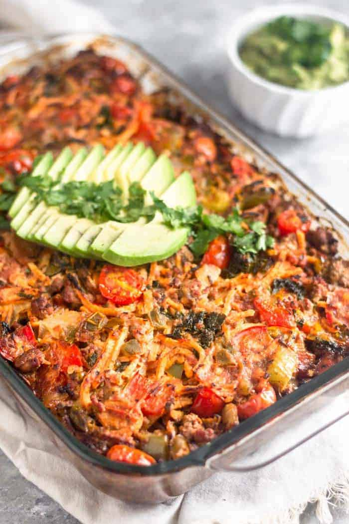 Beef taco casserole angle shot in glass dish with avocado topping - healthy casseroles