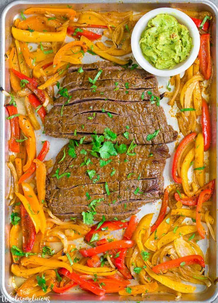 Sheet pan with steak slices in middle surrounded by red and yellow bell pepper slices