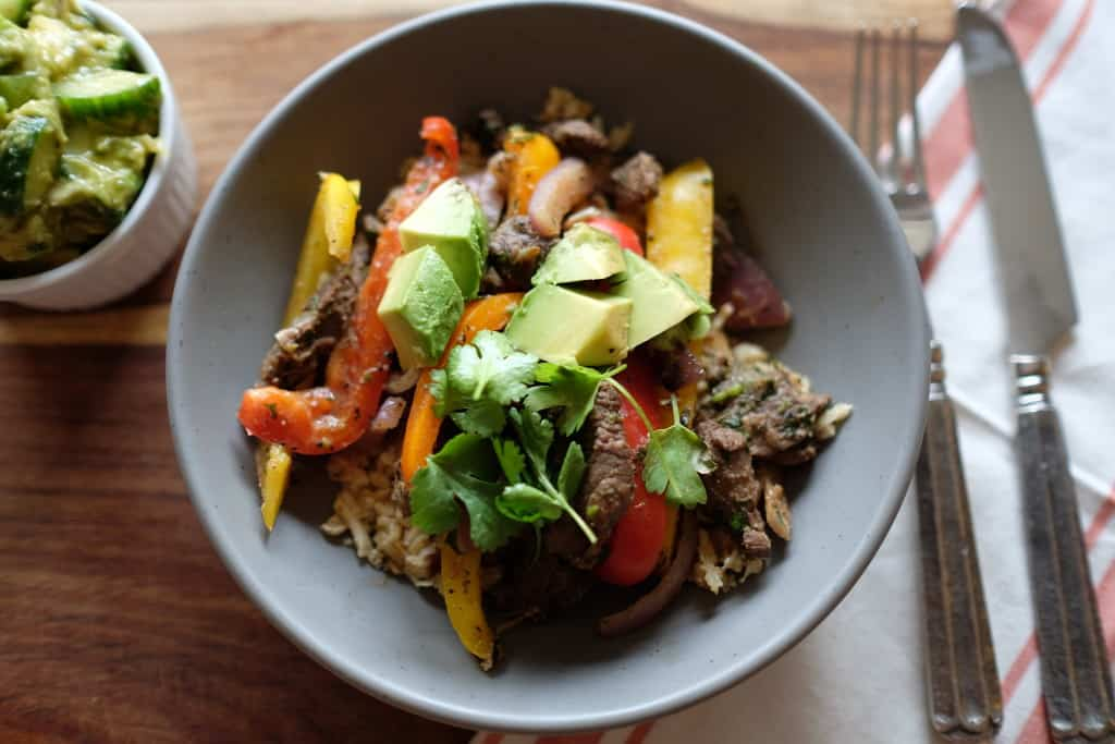 These Paleo steak fajita bowls are so much fun! Served over cauliflower rice, the delicious marinated steak and bell peppers are so EASY to make! Paleo, Gluten-Free and Dairy-Free. | realsimplegood.com