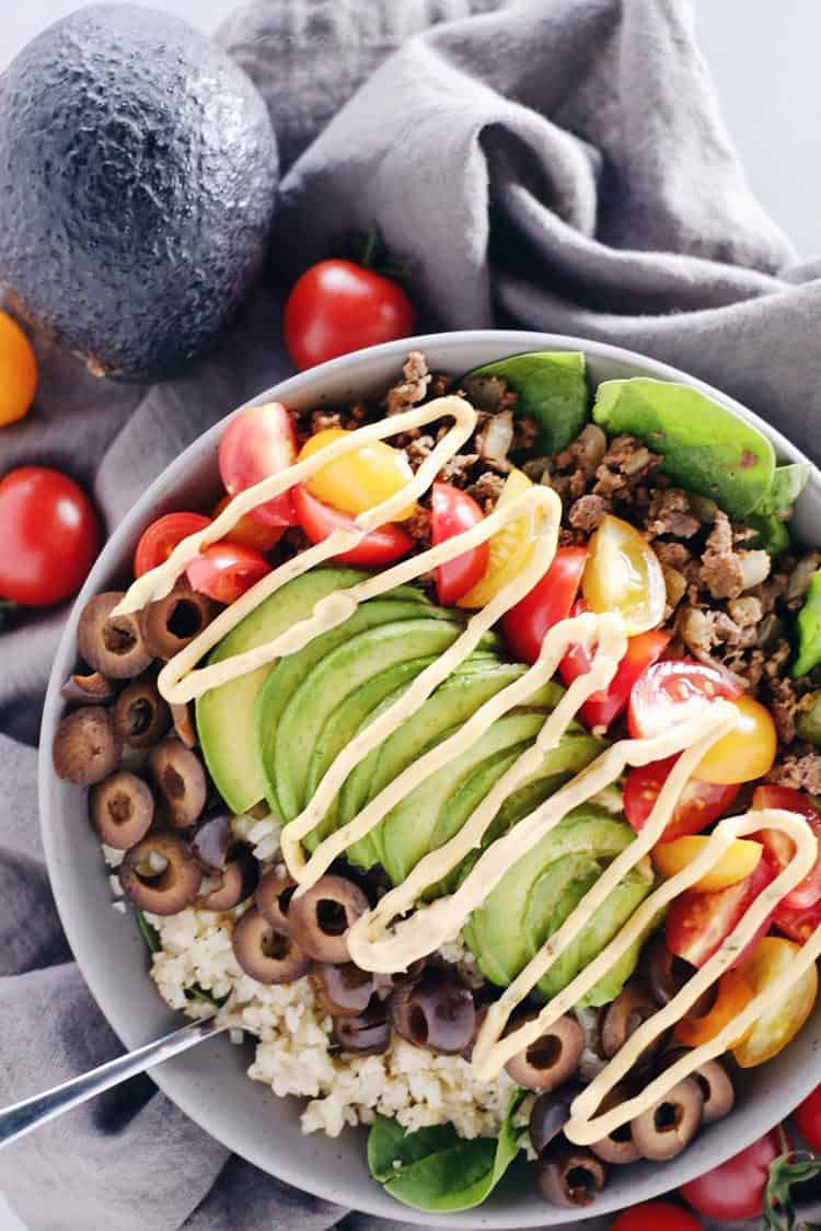Paleo + Whole30 quick and easy ground beef taco bowls are healthy and loaded with flavor. Filled with ground beef, cauliflower rice, spinach and your favorite toppings. Paleo, Gluten-Free, Dairy-Free + Whole 30.   realsimplegood.com