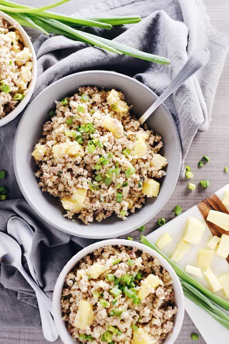 We love this spicy pineapple cauliflower pork fried rice recipe because there are less than 10 ingredients. Paleo + Whole30, it's quick + easy to make! Paleo, Whole30, Gluten-Free + Dairy-Free. | realsimplegood.com
