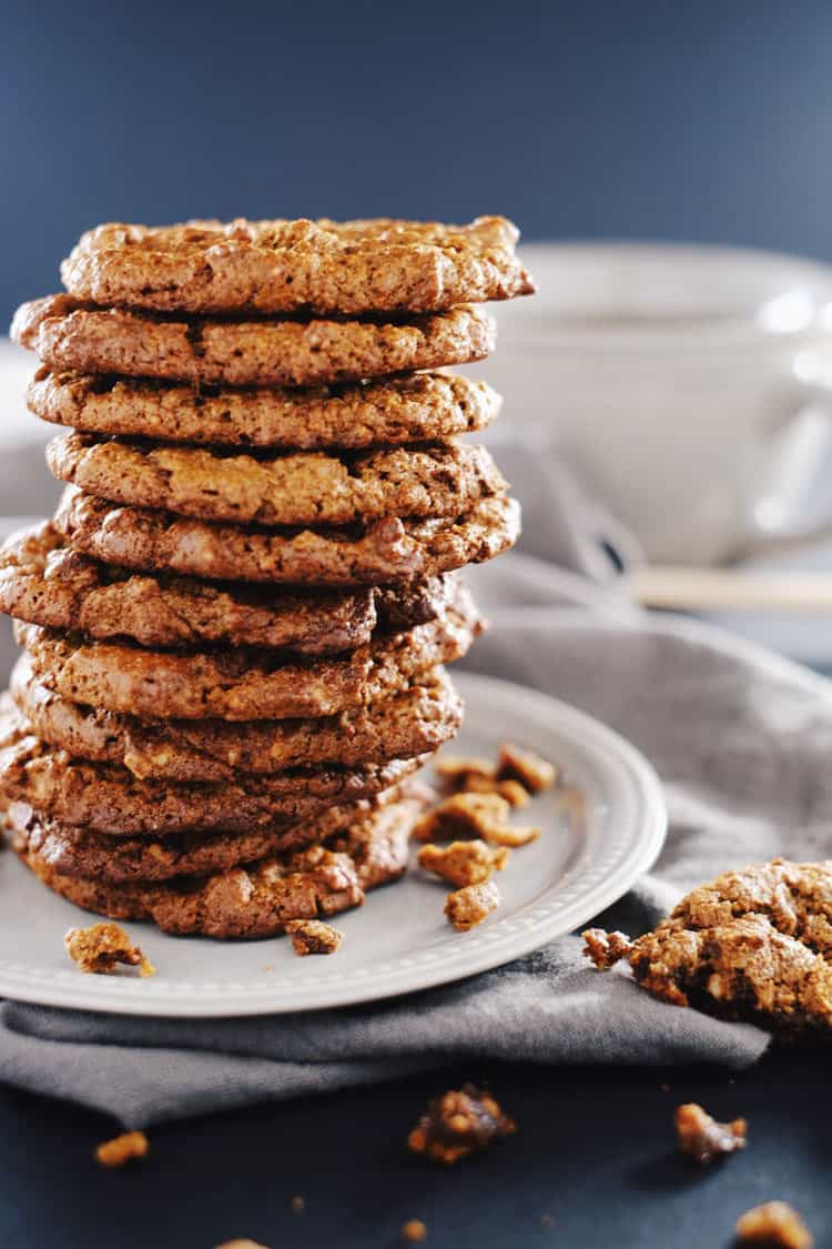 Large stack of cookies on a plate with crumbs around