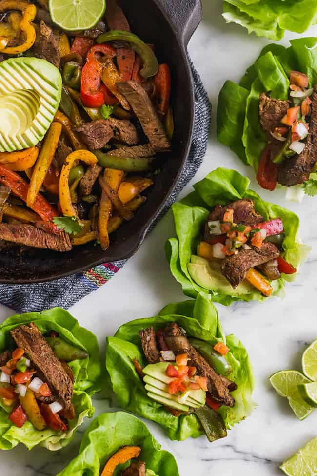 Steak fajita lettuce wraps on marble with pan at top