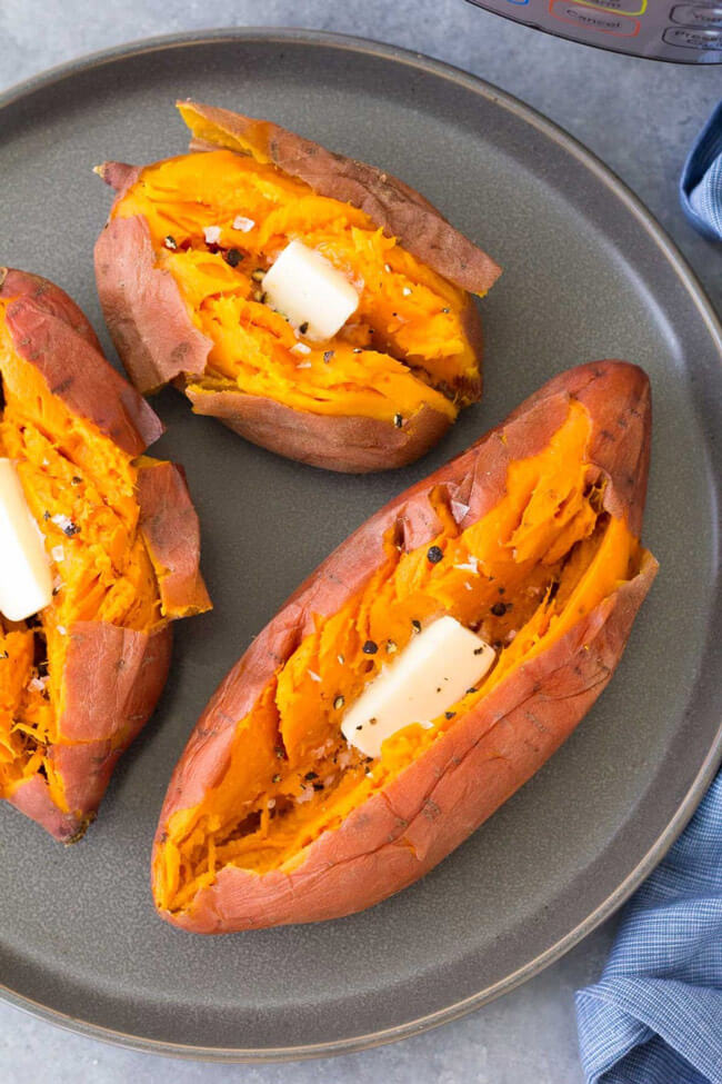 Three sweet potatoes with butter in each on a plate