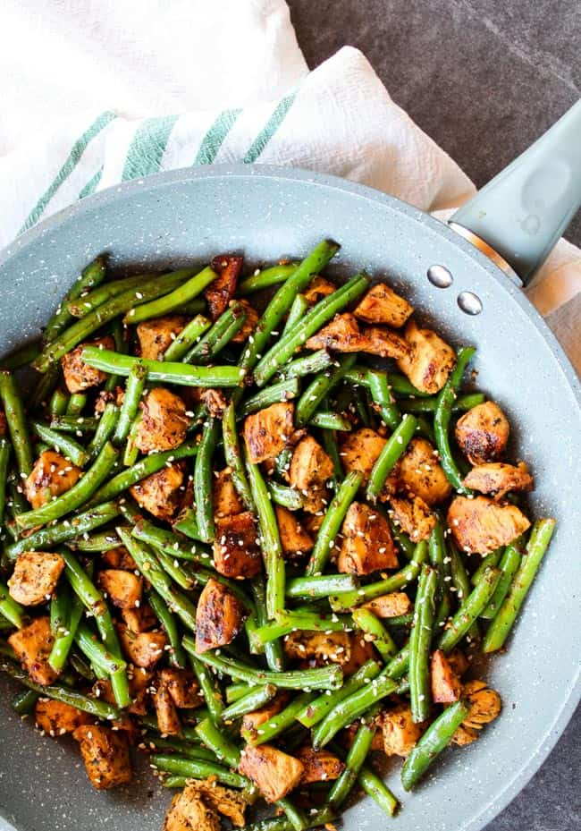 Skillet with small chicken pieces, green beans and sesame seeds