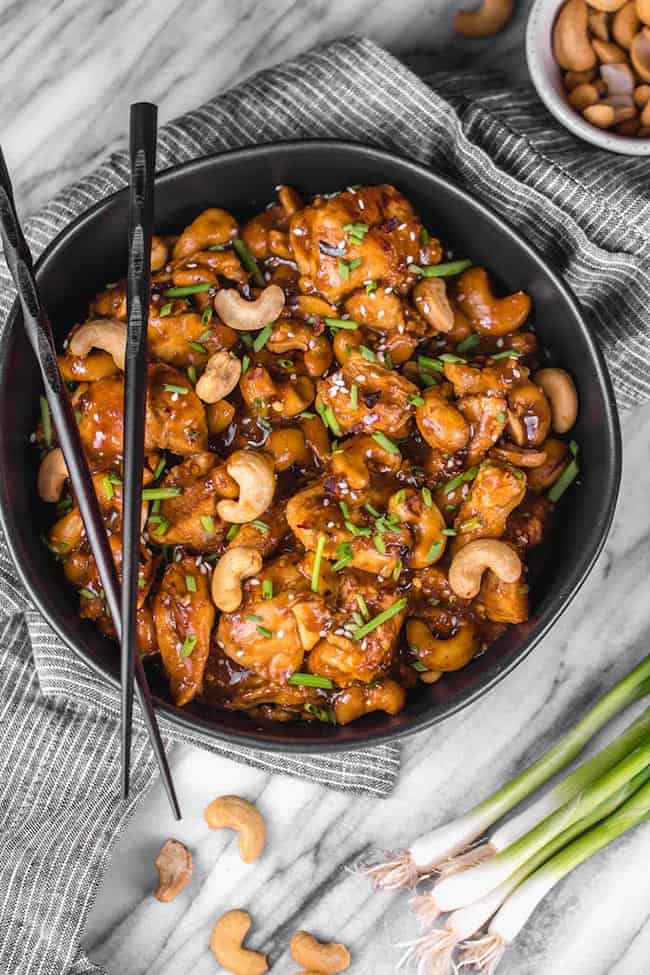 Cashew chicken on plate with chopsticks and diced chives