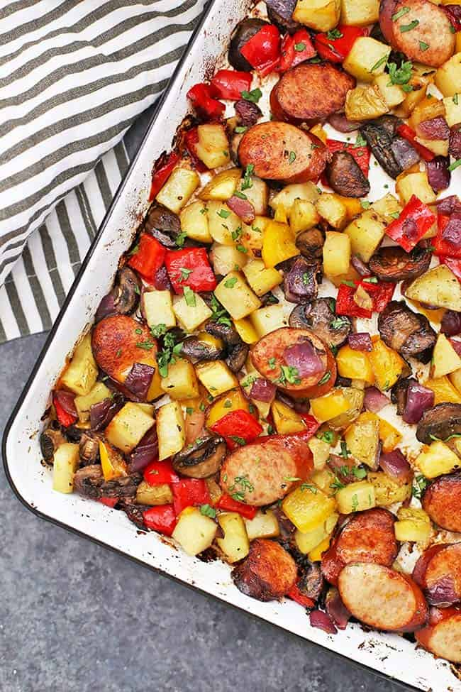 Sheet pan with sausage slices, cubed potatoes, peppers and mushrooms