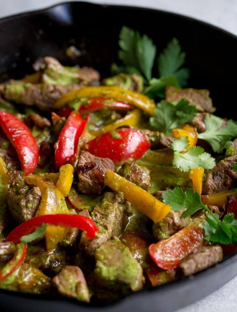 Steak and peppers in skillet with chimichurri sauce