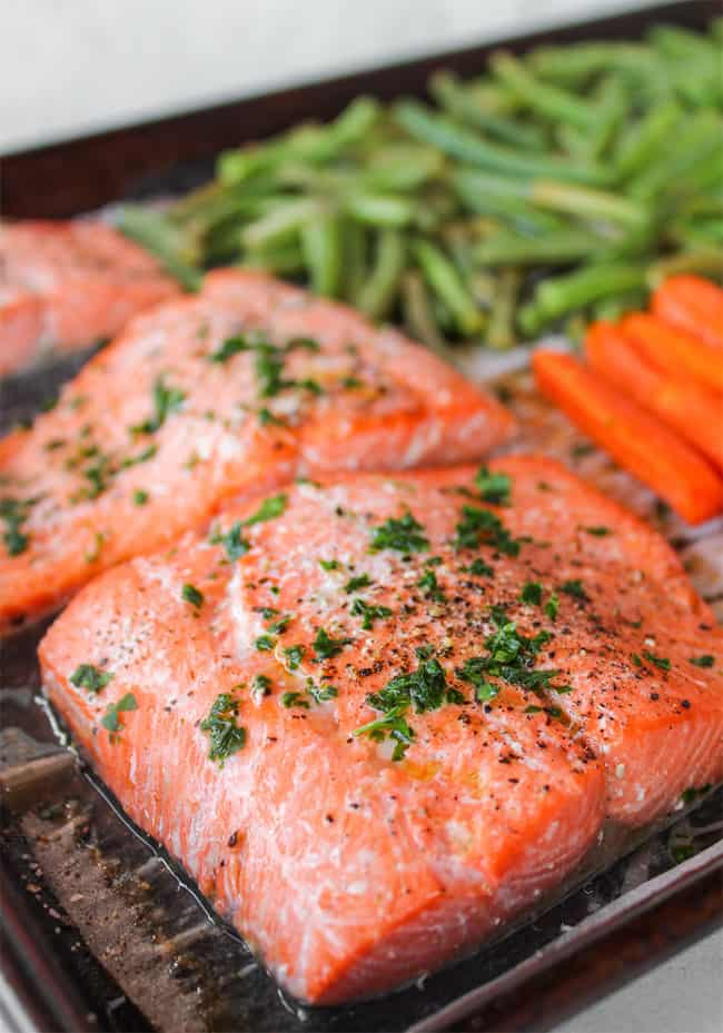 Close up of salmon on sheet pan with green beans and carrots in background