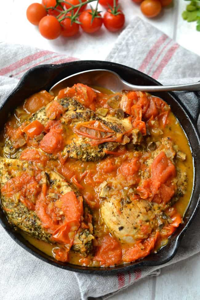 Chicken with tomato sauce in a skillet with spoon