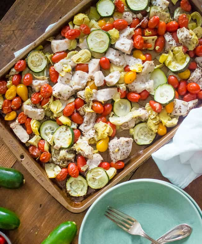 Chicken pieces in sheet pan with zucchini, tomatoes and artichoke hearts