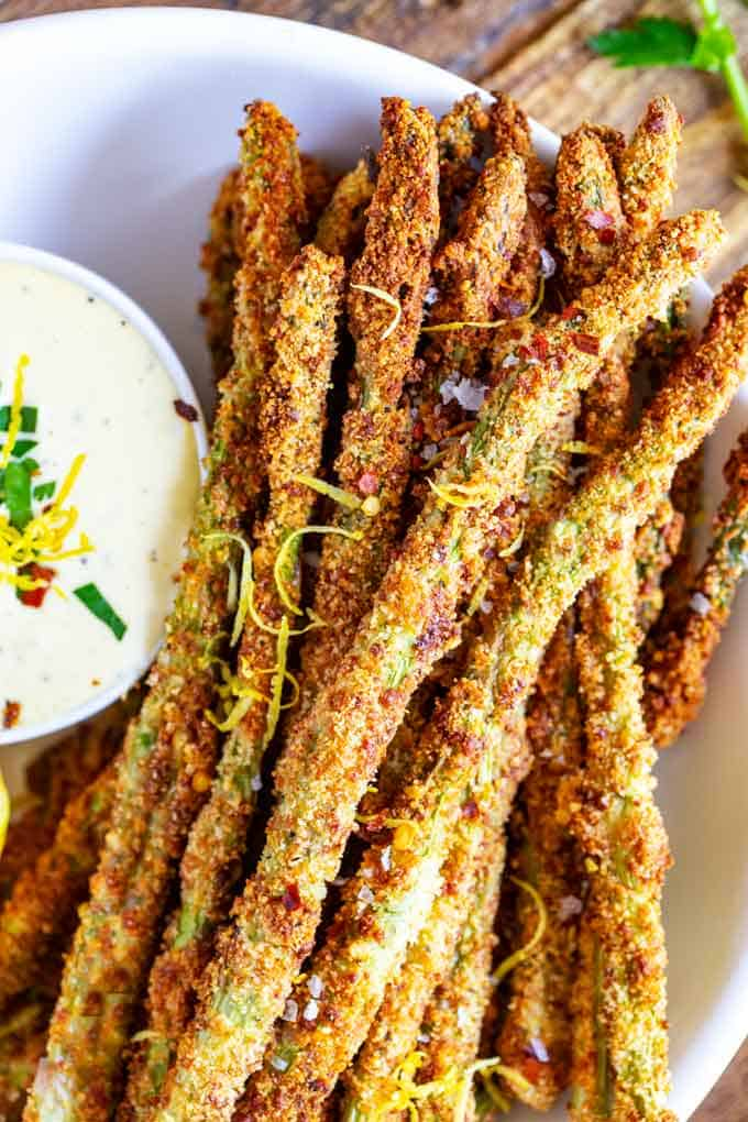 A plate of cheesy asparagus fries with sauce