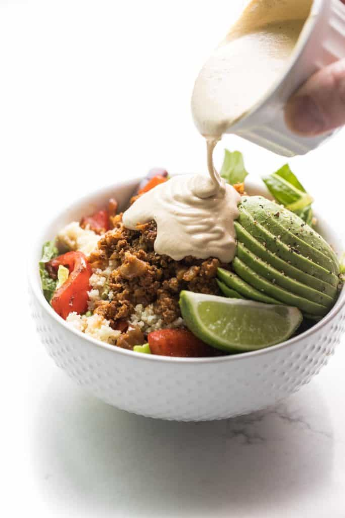 Ground beef burrito bowls with avocado, cauliflower rice and lime. Sauce pouring over the top.