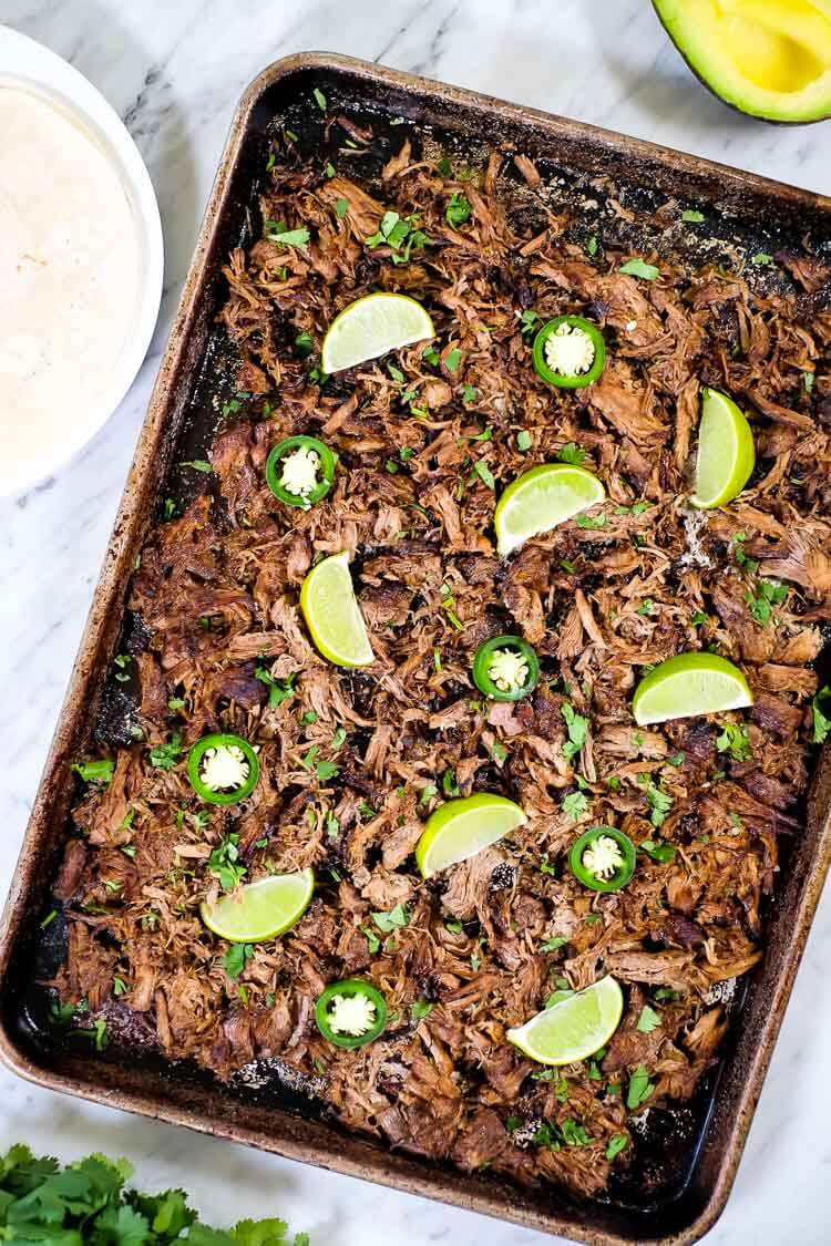 Instant pot carnitas on a sheet pan with limes and jalepeno overhead shot