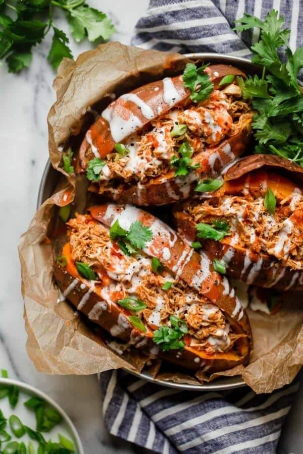 chicken stuffed sweet potatoes with sauce drizzled over the top