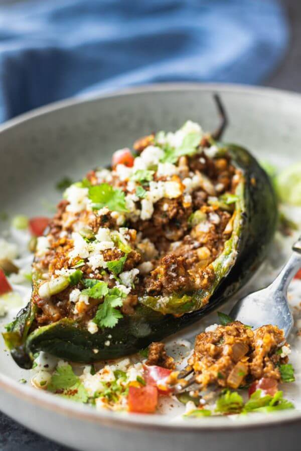 Stuffed poblano pepper on a plate with ground beef and cheese and cilantro topping.