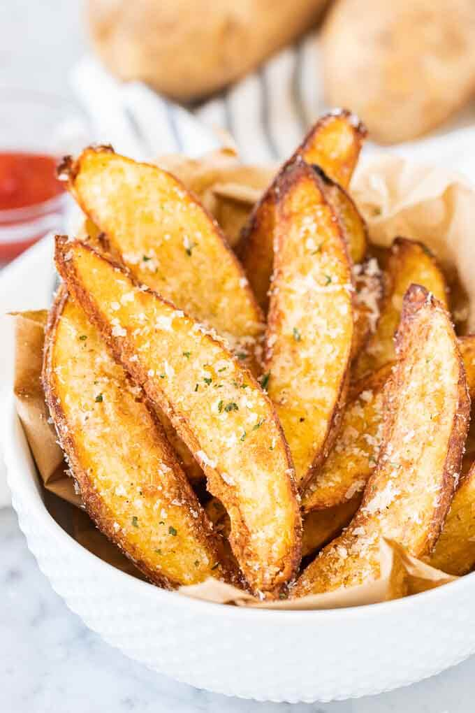 Air fryer potato wedges in a bowl with a sprinkle of parmesan cheese