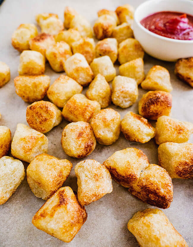 Cauliflower gnocchi nuggets on parchment paper with ketchup