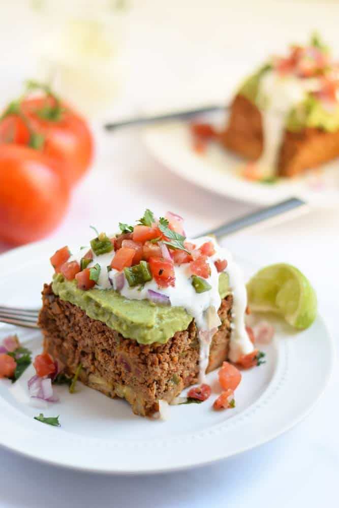 Layered taco casserole piece on plate  with tomato topping and fork - healthy casseroles
