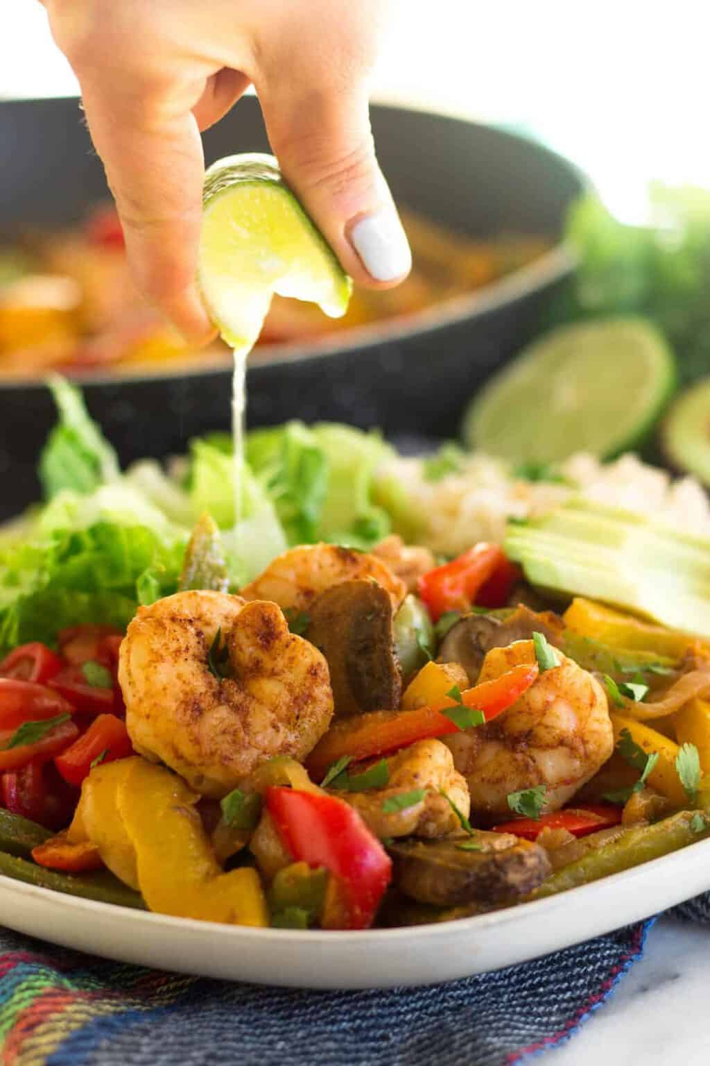 Shrimp fajitas on plate with hand squeezing lime over the top