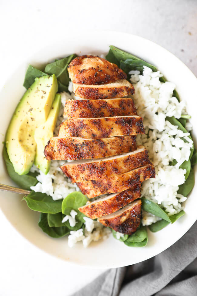 Sliced chicken breasts in a bowl over greens and rice with avocado