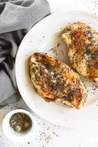 Cooked air fryer chicken breasts on a plate with seasonings