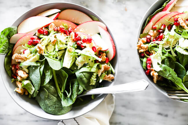 Horizontal image of apple walnut spinach salad in two bowls with forks dug in.