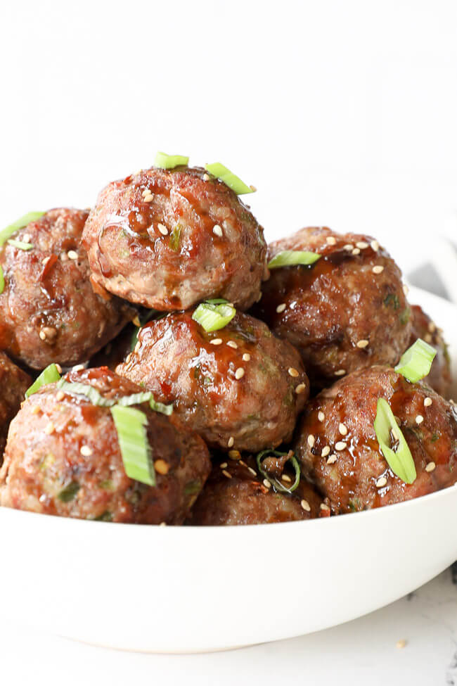 Vertical angled close up image of asian meatballs in a bowl with sauce, green onion and sesame seeds on top.