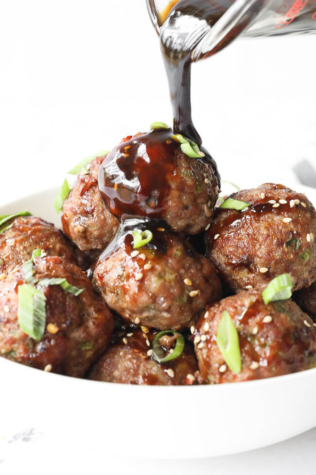 Vertical angled shot of pouring sauce over a bowl of asian meatballs.