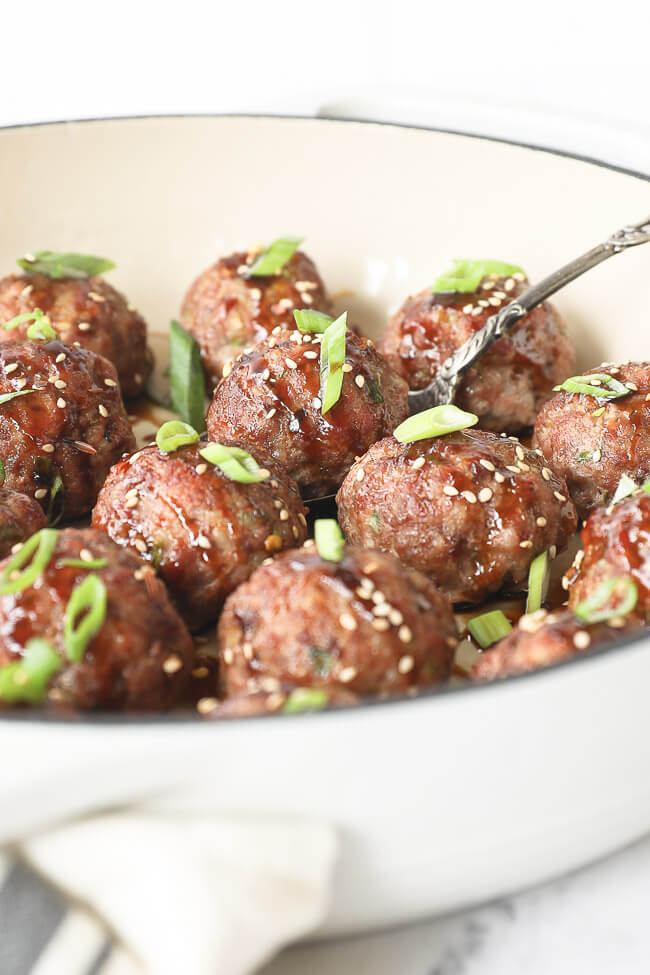 Vertical angled image of asian meatballs in a skillet with serving spoon. Drizzled with sauce and topped with chopped green onion and sesame seeds.