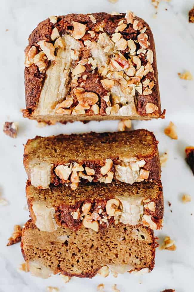 Overhead of banana bread loaf with half cut into slices. Nuts on top.